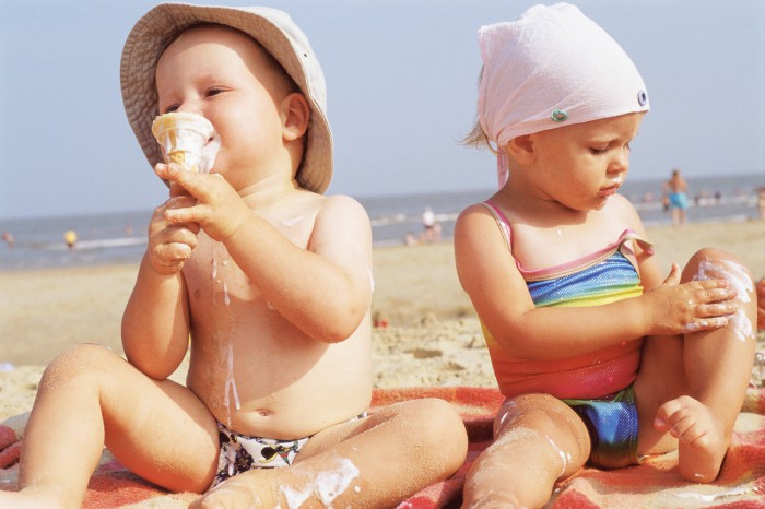 Toddlers having ice cream on the beach