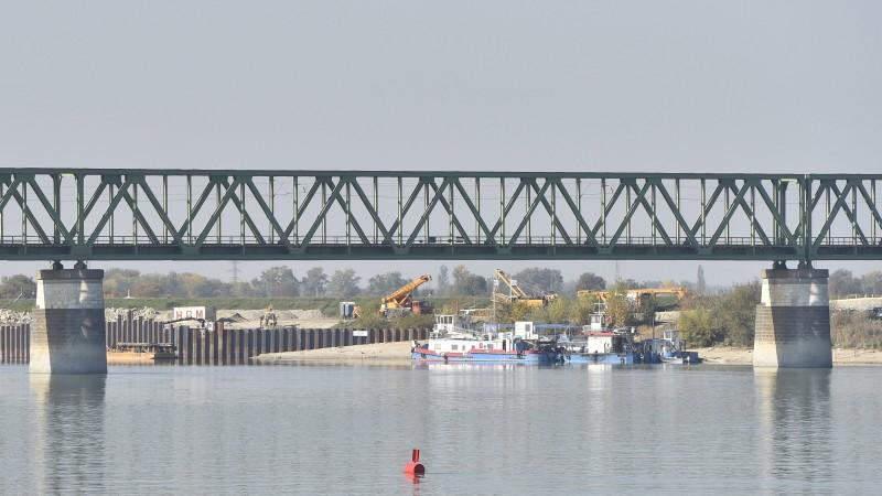 Komárom, 2017. október 17. A háttérben az épülõ új komáromi Duna-híd pillérei a szlovákiai Révkomáromban 2017. október 17-én. Ezen a napon rendezik az új híd létesítésének nyitóünnepségét Komáromban, a Monostori Erõdben, a Dunai-bástyánál a magyar és a szlovák miniszterelnök részvételével. Elõtérben a Duna felett átívelõ, 500 méter hosszú, egyvágányú komáromi vasúti összekötõ híd, amelytõl 170 méterrel nyugatra épül meg az új híd. MTI Fotó: Máthé Zoltán