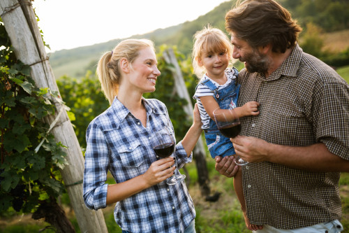 Wine grower family tasting wine in vineyard